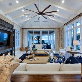 Cette image montre une grande salle de séjour marine ouverte avec un téléviseur encastré, un mur beige et un sol en calcaire.