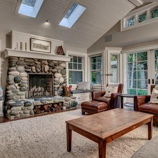 Inspiration pour une salle de séjour marine avec un mur gris, un sol en bois brun, une cheminée standard, un manteau de cheminée en pierre et un sol marron.