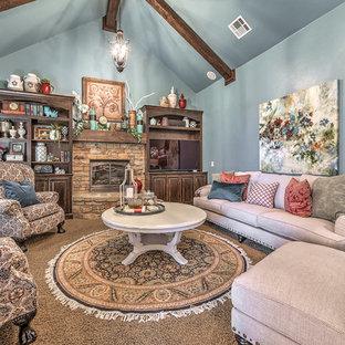 オクラホマシティの中サイズのシャビーシック調のおしゃれなファミリールーム (青い壁、カーペット敷き、標準型暖炉、石材の暖炉まわり、壁掛け型テレビ、ベージュの床) の写真