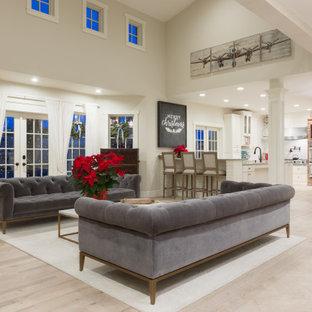 Cette image montre une grande salle de séjour style shabby chic avec un mur blanc, un sol en bois clair, un sol blanc, une cheminée double-face, un manteau de cheminée en bois et un téléviseur dissimulé.