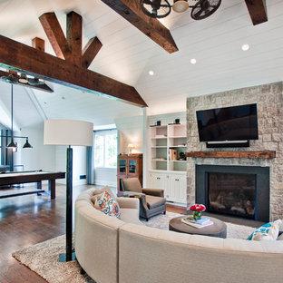 Ejemplo de sala de juegos en casa abierta, extra grande, con paredes blancas, suelo de madera oscura, chimenea tradicional, marco de chimenea de piedra, televisor colgado en la pared y suelo marrón