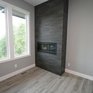 シアトルの中サイズのコンテンポラリースタイルのおしゃれなファミリールーム (グレーの壁、クッションフロア、横長型暖炉、タイルの暖炉まわり、壁掛け型テレビ、グレーの床) の写真