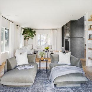 サンディエゴの広い北欧スタイルのおしゃれなオープンリビング (ライブラリー、白い壁、淡色無垢フローリング、両方向型暖炉、漆喰の暖炉まわり、壁掛け型テレビ、ベージュの床) の写真