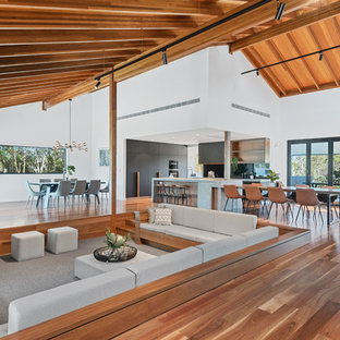 This is an example of a large contemporary open concept family room in Brisbane with medium hardwood floors, white walls and a wood fireplace surround.