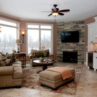 Foto de sala de estar con barra de bar cerrada, tradicional renovada, de tamaño medio, con paredes rosas, suelo de baldosas de cerámica, chimenea de esquina, marco de chimenea de ladrillo, televisor colgado en la pared y suelo beige