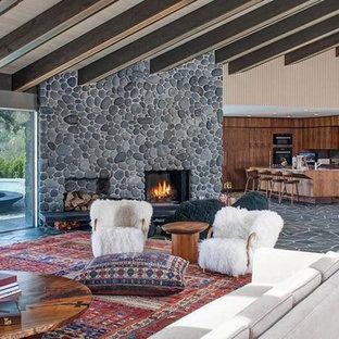 ロサンゼルスの中くらいのミッドセンチュリースタイルのおしゃれなオープンリビング (ベージュの壁、スレートの床、標準型暖炉、石材の暖炉まわり、グレーの床) の写真