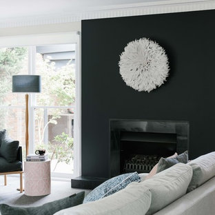This is an example of a mid-sized transitional open concept family room in Melbourne with black walls, carpet, a standard fireplace, a tile fireplace surround and grey floor.