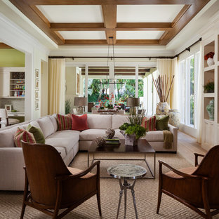 Family room - transitional medium tone wood floor and brown floor family room idea in Miami with beige walls and a media wall