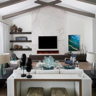 マイアミの広いビーチスタイルのおしゃれなオープンリビング (白い壁、石材の暖炉まわり、壁掛け型テレビ、茶色い床、無垢フローリング、横長型暖炉) の写真
