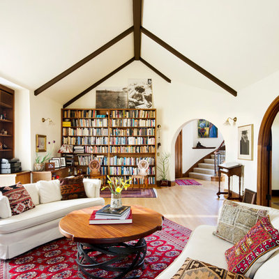 Example of a tuscan medium tone wood floor family room design in San Francisco with white walls