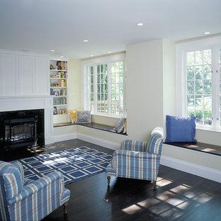 Esempio di un soggiorno tradizionale di medie dimensioni e chiuso con pareti gialle, parquet scuro, camino classico, cornice del camino in legno e parete attrezzata
