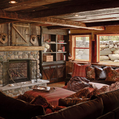Family room - rustic enclosed dark wood floor family room idea in Minneapolis with brown walls, a standard fireplace and a stone fireplace