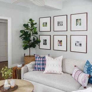フィラデルフィアの中サイズのトランジショナルスタイルのおしゃれなファミリールーム (グレーの壁、無垢フローリング、標準型暖炉、石材の暖炉まわり、壁掛け型テレビ、茶色い床) の写真
