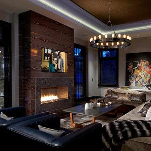 Großes, Offenes Modernes Wohnzimmer mit grauer Wandfarbe, dunklem Holzboden, Gaskamin, Wand-TV und Kaminumrandung aus Stein in New York