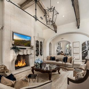 Diseño de sala de estar con barra de bar abierta, romántica, extra grande, con paredes blancas, suelo de madera en tonos medios, chimenea tradicional, marco de chimenea de piedra, televisor colgado en la pared y suelo marrón