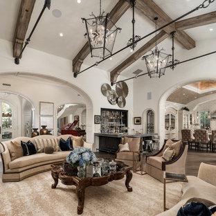 Modelo de sala de estar con barra de bar abierta, romántica, extra grande, con paredes blancas, suelo de madera en tonos medios, chimenea tradicional, marco de chimenea de piedra, televisor colgado en la pared y suelo marrón