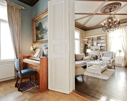 example of a classic family room design in other with beige walls
