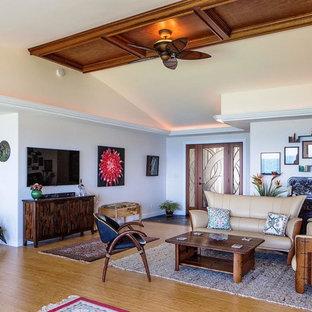 Exemple d'une grande salle de séjour exotique ouverte avec un mur blanc, un sol en bois clair, aucune cheminée et un téléviseur fixé au mur.