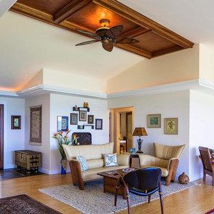 Réalisation d'une grande salle de séjour ethnique ouverte avec un mur blanc, un sol en bois clair, aucune cheminée et un téléviseur fixé au mur.