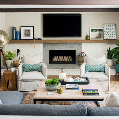 Eclectic medium tone wood floor and brown floor family room photo in Los Angeles with white walls, a standard fireplace, a concrete fireplace and a wall-mounted tv