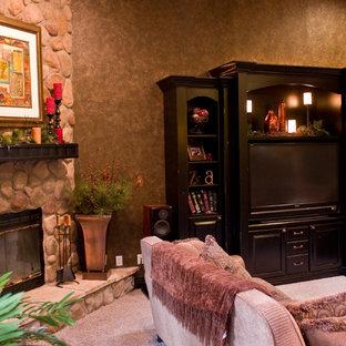 デンバーの中サイズのトラディショナルスタイルのおしゃれなファミリールーム (マルチカラーの壁、カーペット敷き、コーナー設置型暖炉、石材の暖炉まわり、埋込式メディアウォール、ベージュの床) の写真