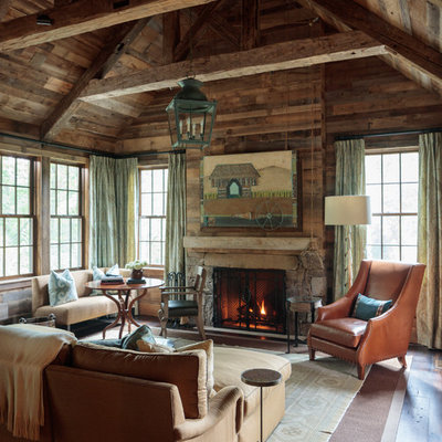 Family room - rustic dark wood floor and brown floor family room idea in Other with brown walls, a standard fireplace and a stone fireplace