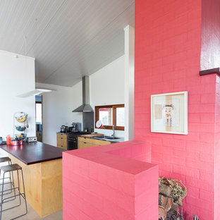 Inspiration for a small contemporary open concept concrete floor family room remodel in Sydney with a standard fireplace, a brick fireplace and pink walls