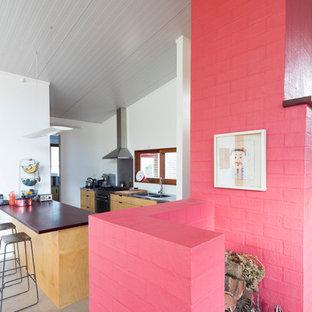 Cette photo montre une petite salle de séjour tendance ouverte avec béton au sol, une cheminée standard, un manteau de cheminée en brique et un mur rose.