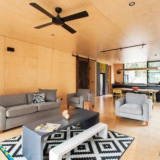 На фото: открытые гостиные комнаты в современном стиле с бежевыми стенами, полом из фанеры и печью-буржуйкой