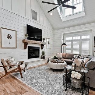 Inspiration för stora lantliga allrum med öppen planlösning, med vita väggar, en standard öppen spis, en spiselkrans i trä, en väggmonterad TV, mellanmörkt trägolv och brunt golv
