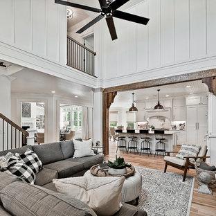 Imagen de sala de estar abierta, de estilo americano, grande, con paredes blancas, suelo de madera clara, chimenea tradicional, marco de chimenea de madera y televisor colgado en la pared
