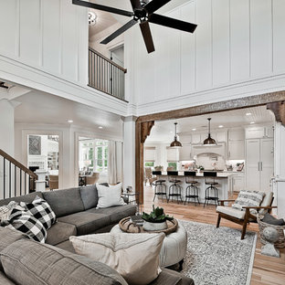 Example of a large arts and crafts open concept light wood floor family room design in Other with white walls, a standard fireplace, a wood fireplace surround and a wall-mounted tv