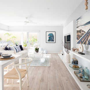Beach style open concept family room in Brisbane with white walls and a built-in media wall.