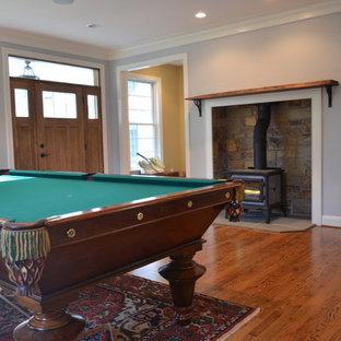フィラデルフィアの大きいトランジショナルスタイルのおしゃれなファミリールーム (ゲームルーム、青い壁、無垢フローリング、テレビなし、薪ストーブ、茶色い床) の写真