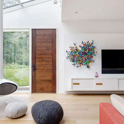 Mid-sized trendy open concept light wood floor and beige floor family room photo in Boston with white walls, a hanging fireplace and a wall-mounted tv