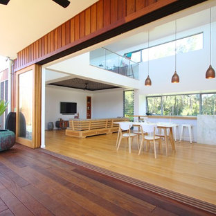 Family room - large contemporary light wood floor family room idea in Sydney with white walls and a wall-mounted tv