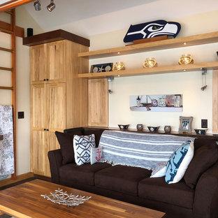 Diseño de sala de juegos en casa cerrada, costera, pequeña, sin chimenea, con paredes beige, suelo de madera clara, televisor colgado en la pared y suelo marrón