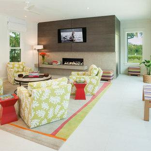 タンパの大きいビーチスタイルのおしゃれな独立型ファミリールーム (白い壁、磁器タイルの床、横長型暖炉、石材の暖炉まわり、埋込式メディアウォール) の写真