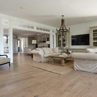 Cette image montre une salle de séjour marine de taille moyenne et ouverte avec un mur blanc, aucune cheminée, un téléviseur fixé au mur, un sol marron et un sol en bois brun.