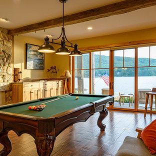 Diseño de sala de juegos en casa costera con paredes amarillas, suelo de madera en tonos medios y suelo marrón