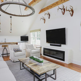 Example of a farmhouse medium tone wood floor and brown floor family room design in Raleigh with a bar, white walls, a ribbon fireplace and a wall-mounted tv