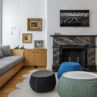 ボストンのトランジショナルスタイルのおしゃれなファミリールーム (白い壁、淡色無垢フローリング、標準型暖炉、壁掛け型テレビ) の写真