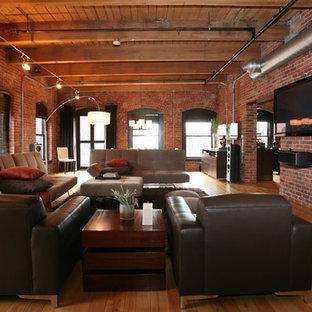 Foto de sala de estar abierta, industrial, con paredes rojas, suelo de madera en tonos medios y televisor colgado en la pared