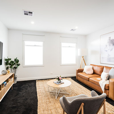 Example of a mid-sized trendy open concept carpeted and black floor family room design in Melbourne with white walls, no fireplace and a wall-mounted tv