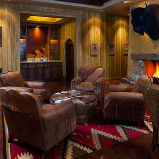 Family room - rustic enclosed family room idea in Other with a bar, brown walls, a standard fireplace and a stone fireplace