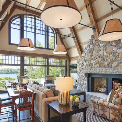 Large mountain style open concept medium tone wood floor and brown floor family room photo in Minneapolis with a standard fireplace, beige walls, a stone fireplace and no tv