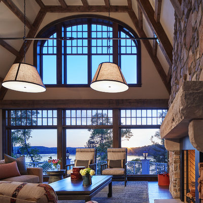 Example of a large mountain style open concept medium tone wood floor and brown floor family room design in Minneapolis with a standard fireplace, a stone fireplace, beige walls and no tv
