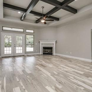 ダラスの中サイズのモダンスタイルのおしゃれなファミリールーム (グレーの壁、淡色無垢フローリング、コーナー設置型暖炉、タイルの暖炉まわり、壁掛け型テレビ、茶色い床) の写真