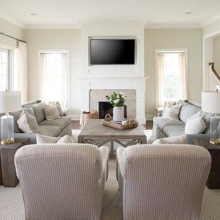 Cette photo montre une salle de séjour chic de taille moyenne et ouverte avec un mur gris, un sol en bois foncé, une cheminée standard, un manteau de cheminée en pierre, un téléviseur fixé au mur et un sol marron.