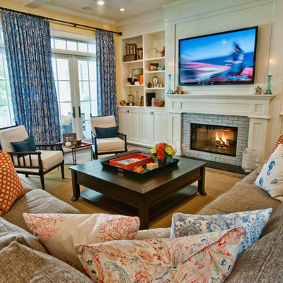 Example of a classic family room design in Los Angeles with yellow walls, a standard fireplace and a media wall